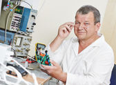 Technician engineer at work with microchip — Stock Photo
