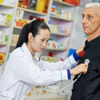 Chinese pharmacy woman with patient — Stock Photo