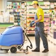 Worker cleaning store floor with machine — Stock Photo #30979471