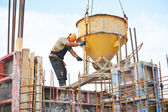 Building workers pouring concrete with barrel — Stock Photo