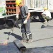 Flat roof covering repair works with roofing felt — Stockfoto