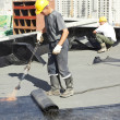 Flat roof covering repair works with roofing felt — ストック写真