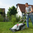 Man mowing lawn in backyard — Stock Photo #32582283