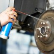 Stock Photo: Auto mechanic at car suspension repair work
