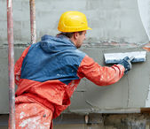 Builder at facade plastering works — Stock Photo