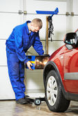 Auto mechanic at car headlight checkup — Stock Photo