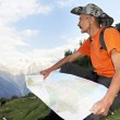 Tourist hiker with map in mountains — Stock Photo