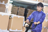 Chinese warehouse worker with forklift stacker — Stock Photo