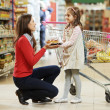 Woman and little girl shopping fruits — Stock Photo #36837787
