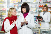 Pharmacist helps to drug purchaser — Stock Photo