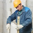 Construction mason worker bricklayer with level — Stock Photo