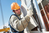 Builder at aerated facade tile installation — Stock Photo