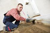 Plasterer concrete worker at floor work — Stock Photo