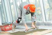 Tiler at industrial floor tiling renovation work — Stock Photo