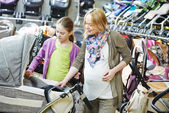 Pregnant woman chosing pram — Stock Photo