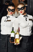 Waitress girl in mask with bottle — Stockfoto