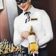 Waitress girl in mask with bottle — Stock Photo #37867325