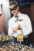 Waitress girl in mask with bottle — Stock Photo