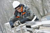 Worker polishing metal fence barrier — Stock Photo