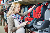 Woman choosing child car seat — Stockfoto