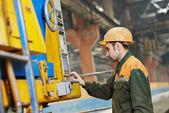 Industrial worker operating machine — Stock Photo