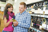 Family choosing wine in supermarket — Stock Photo