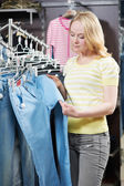 Young woman at clothes shopping store — Stock Photo