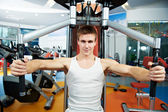 Positive man at chest pectoral exercises machine — Stock Photo