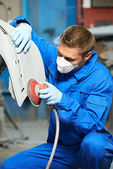 Auto mechanic polishing car body — Stock Photo