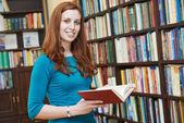 молодая женщина с книгой в библиотеке — Стоковое фото