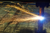 Laser or plasma cutting of metal sheet with sparks — 图库照片