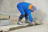 Carreleur à la rénovation de carrelage de sols industriels — Photo