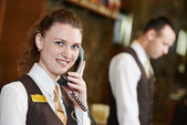 Hotel worker with phone on reception — Stock Photo