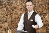 Hotel worker with key card — Stock Photo