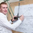 Designer making construction project by pencil on drawing board — Stock Photo #13260409