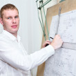Engineer with blueprint standing near old drawing board — Stock Photo