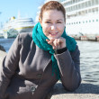 Woman in coat standing on city embankment with cruise ship on background — Stock Photo #13260464
