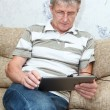 Elderly man connected on internet with electronic tab — Stock Photo