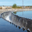 Close up of water overflowing from circular storage tank - Stock Photo