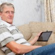 Elderly man connected on internet with electronic tab — Stock Photo #13260627