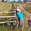 Young woman villager standing in front of wooden fence with her doughter — Foto Stock