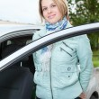 Young pretty woman standing bear a car with opened door — Stock Photo