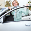 Young pretty woman standing behind a car with opened door — Stock Photo