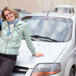 Stock Photo: Young pretty Caucasain womstanding behind new own car