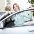 Young pretty Caucasain woman standing behind a car with opened door — Stock Photo