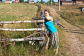 Young woman villager standing in front of wooden fence — Stock Photo