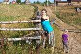 Young woman villager standing in front of wooden fence with her doughter — Stock Photo