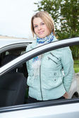 若いきれいな女性立っているクマ開いたドアが付いている車 — ストック写真