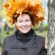 Attractive young woman with maple wreath standing near birch tree — Stock Photo