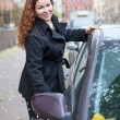 Happy Caucasian woman holding car door handle to sitting in vehicle — Stock Photo